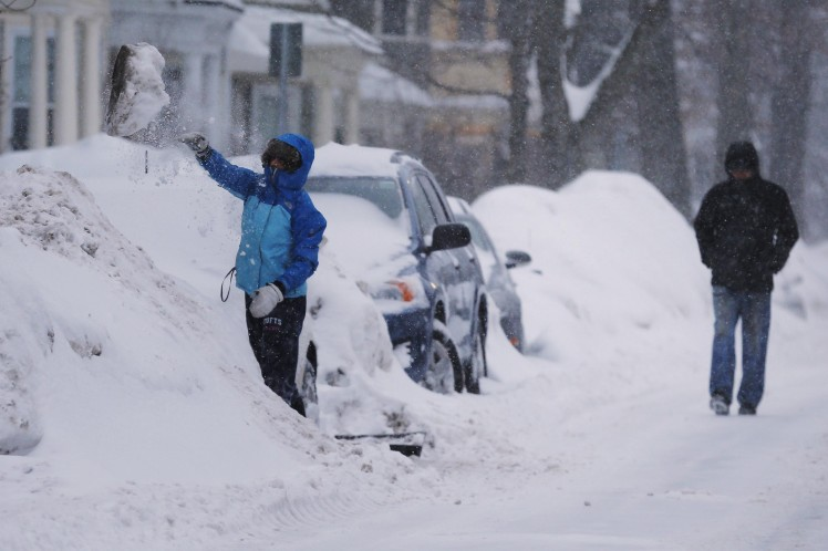 A driver throws aside a clump of snow while digging out their car during a winter snow storm in Cambridge