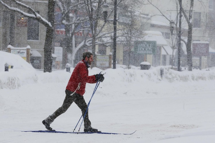 A man skis across an intersection during a winter snow storm in Brookline
