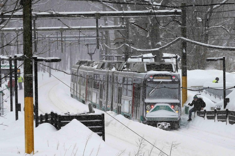 An MBTA green line subway train sits at a station during a winter snow storm in Brookline
