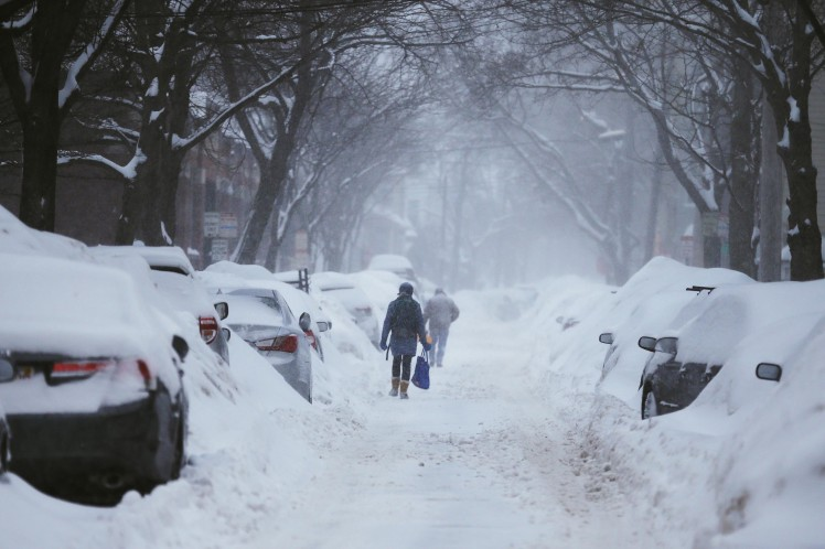 Pedestrians make their way along a snow covered street during a winter snow storm in Cambridge