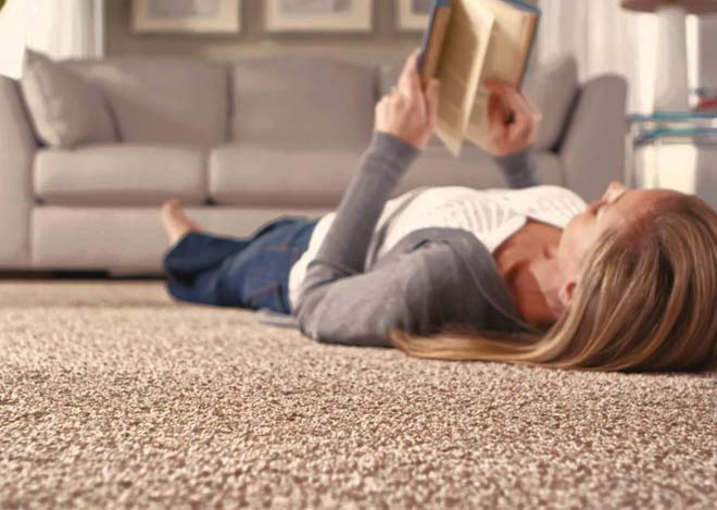 woman with book laying on mohawk smartstrand carpet