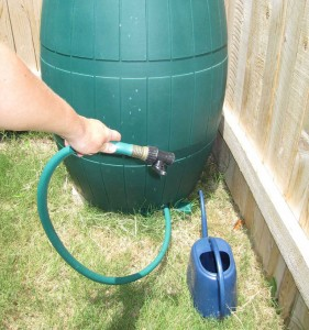 man filling a watering can from rain barrel